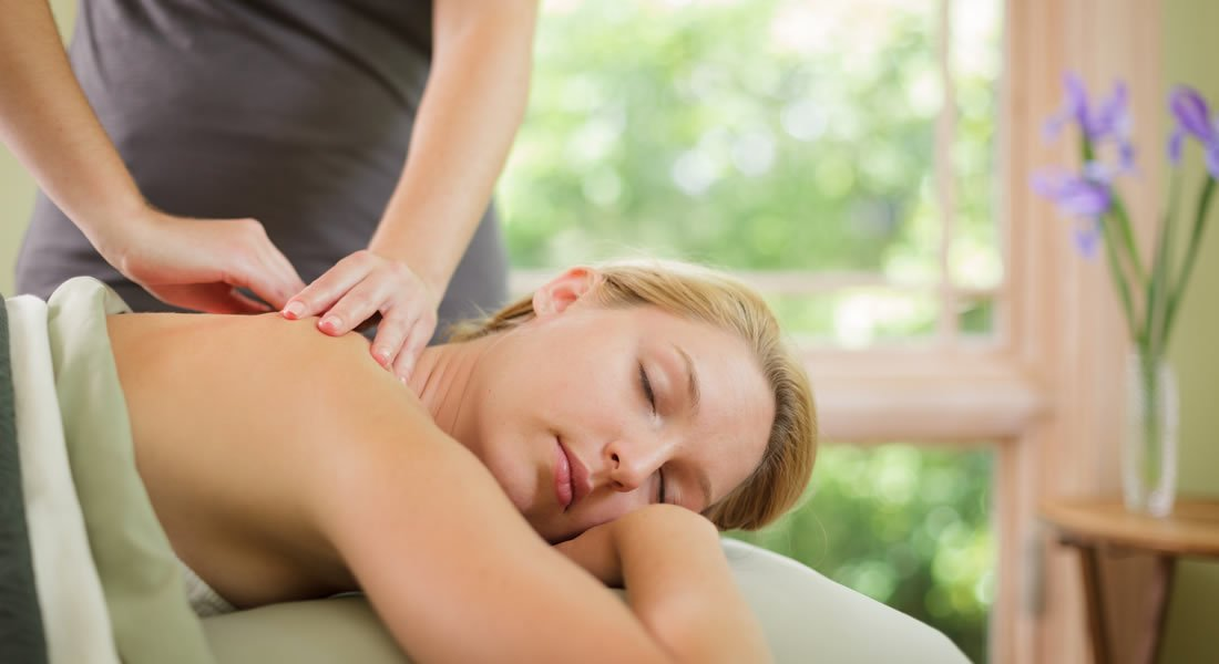 Women laying on her stomach getting a back massage