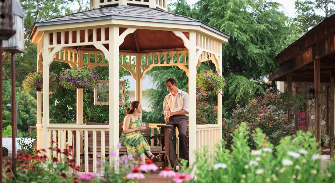 A couple sitting in the gazebo with flowers and greenery all around