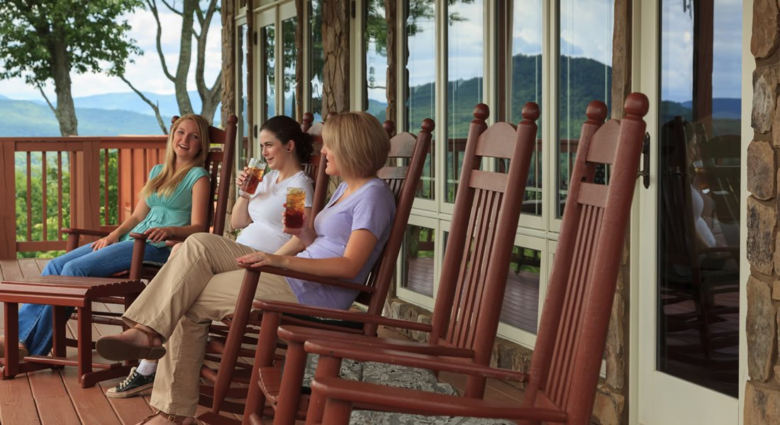 Three women sitting on the porch in brown rocking chairs