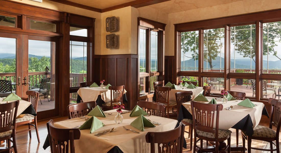 Dining room with white table cloths and green napkins with windows on two sides with view of the mountains.
