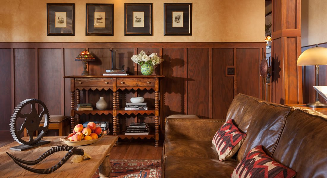Sitting area with Leather couch  coffee table with apples, wood panels half way up the wall