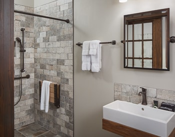 Square grey stone Shower with the stone continuing on the bathroom floor. Floating white sink outlined in wood