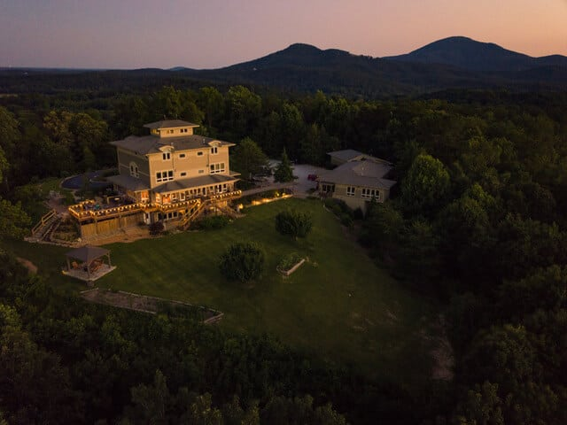 An ariel shot of the inn with the sun setting on the back side of the Inn with the mountains all around the property. A Stunning View