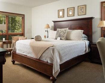 California King bed with White bedspread, Wood frame bed with High Headboard. Large windows with a view of the mountains