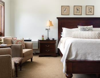 Two Tan chairs to the left and to the right is the Wooden California King bed with a white bedspread, night stand inbetween