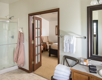 Chair with fluffy white towels next to  the sink. Glass inclosed shower with a view of the bedroom