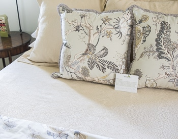 Upclose of the flora pillows on the tan bedspread