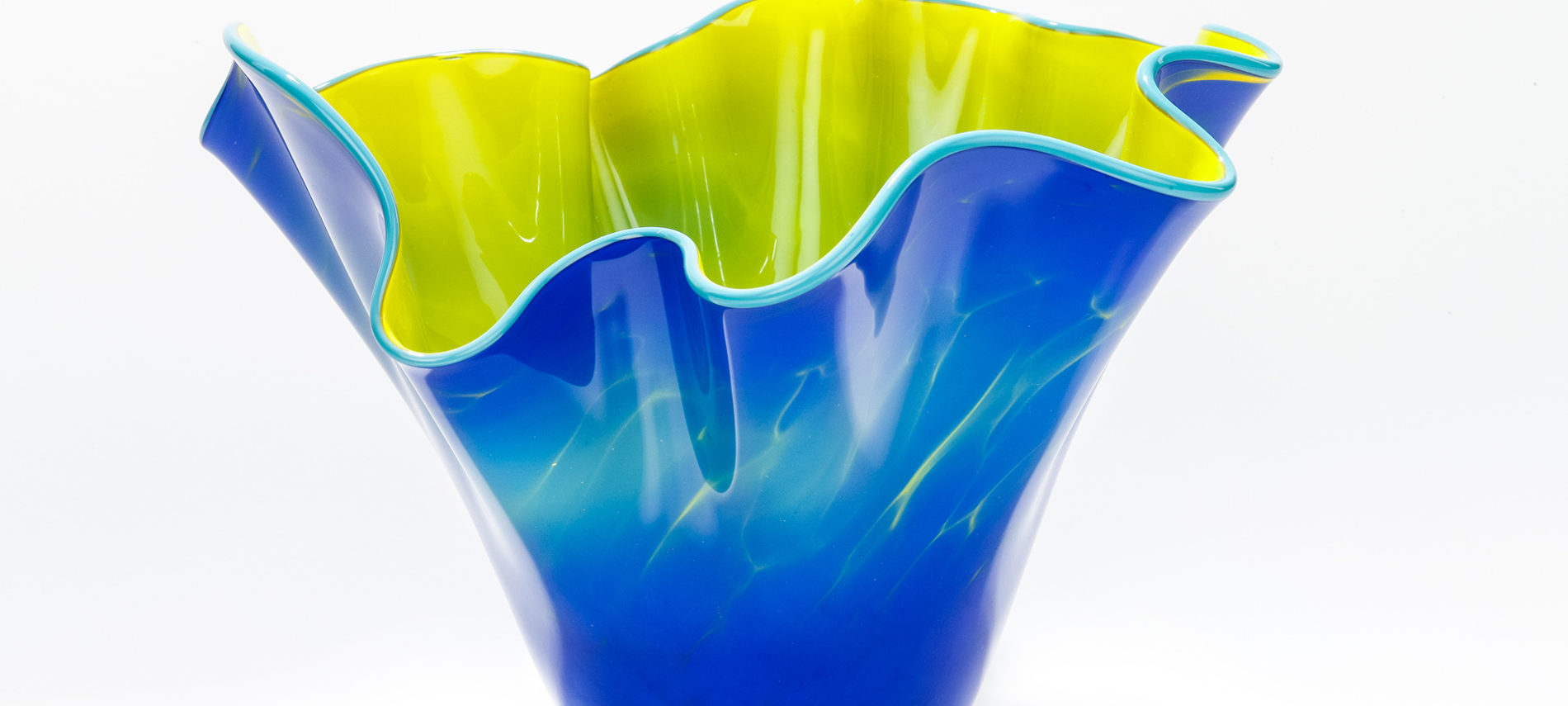 Fluted blue and yellow glass vase on a white backgrounds
