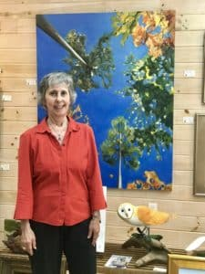 One of the artists standing next to her colorful painting.