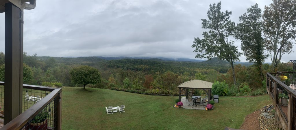 A view from the deck of Lucille's, a lush, green landscape with rolling hills and a gazebo below.