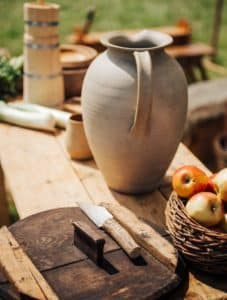 Ceramic jug sits on a wooden table surrounded by tools and a basket of apples.