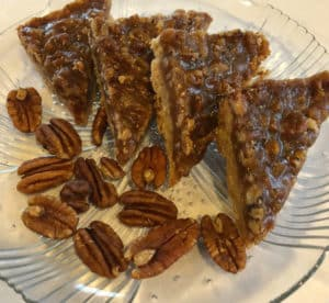Slices of pecan bars on a glass plate.