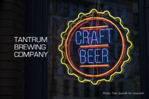 "Neon beer sign that says ""Craft Beer"" with title ""Tantrum Brewing Company""."