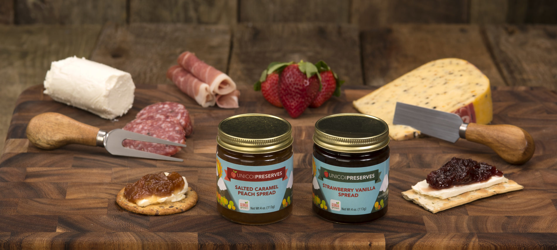 A photo of two jars of spreads with an assortment of crackers, cheeses, and sausages. Red strawberries, ham all on a large cutting board ,