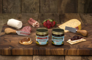 a wood board with display of cheeses, sausages, and jams.