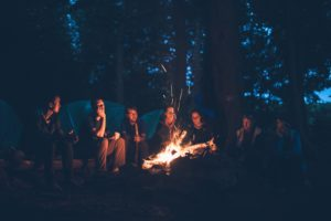 Friends are gathered around a campfire at nighttime.