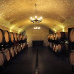 A photo inside the wine cave, showing a warm golding setting with walls lined with wine barrels.