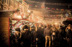 A crowd of people at an outdoor Christmas festival with lights framing the buildings and hanging across the streets.