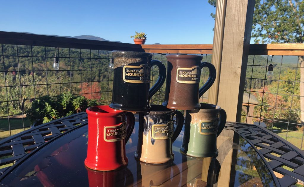 Five mugs stacked two over three on a table on Lucille's back porch overlooking the mountains.