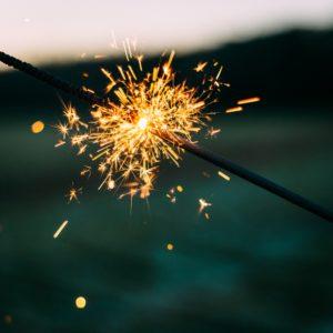 A lit sparkler firework emitting orange sparks.