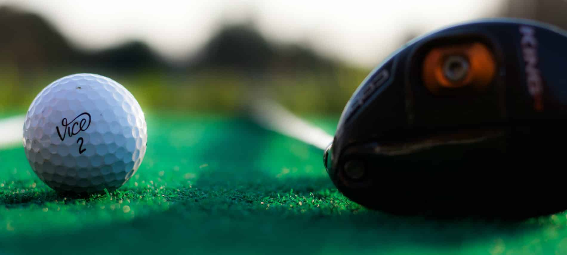 The head of a driver next to a golf ball on the green.