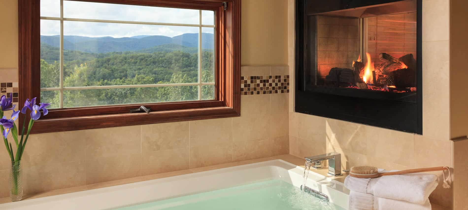 soaking tub full with water, built in gas fireplace with a window with a view of the mountains