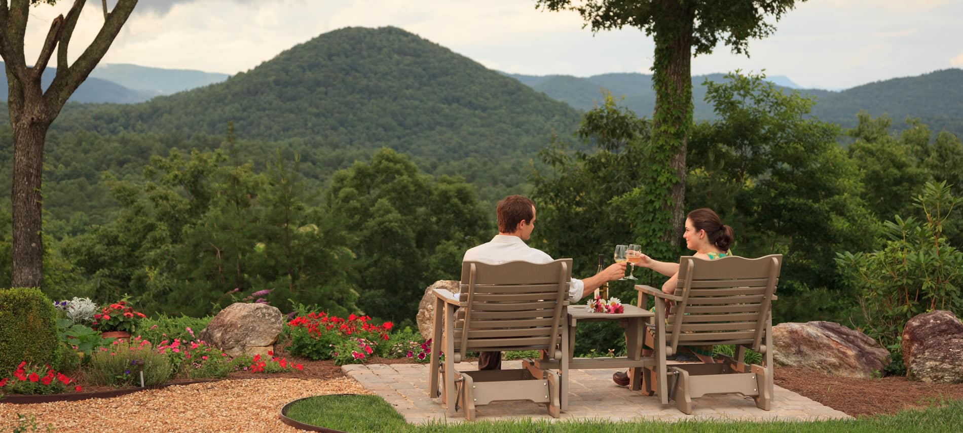 a couple sitting in the wooden chairs outside on a patio looking out at the Mountains