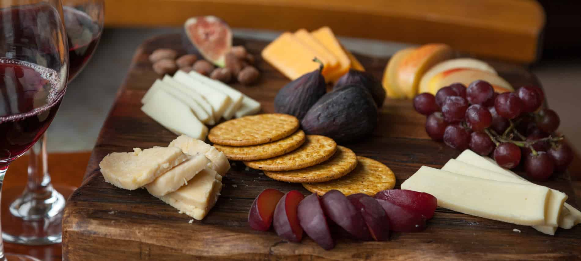 cutting board with Grapes, Dates, Crackers, Yellow cheese, White cheese and two glasses of red wine