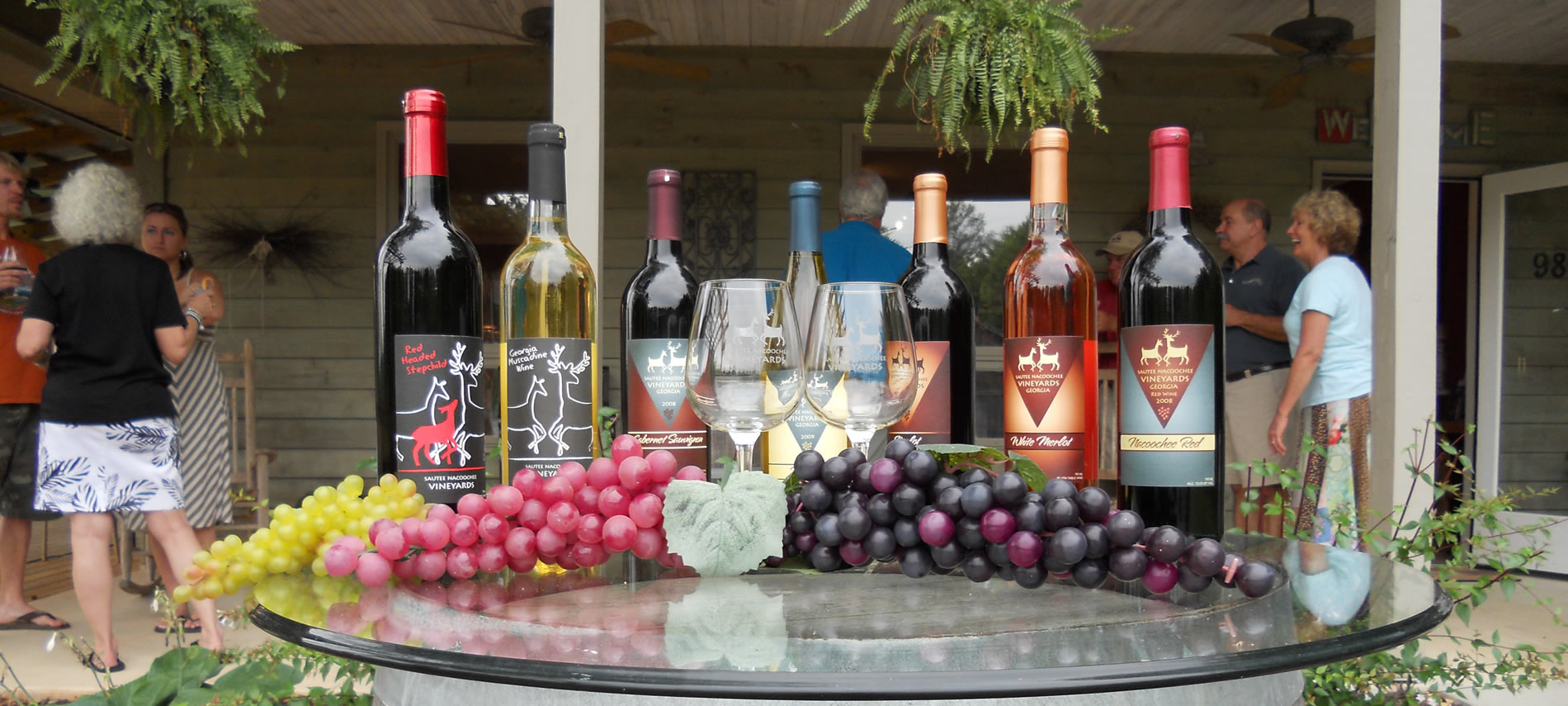Seven bottles of different wines on a glass table with Red Grapes, Greeen Grapes and black grapes.