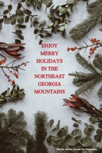 A pictur frame made with holly boughs and inside is written: Enjoy merry holidays in the northeast Georgia mountains.