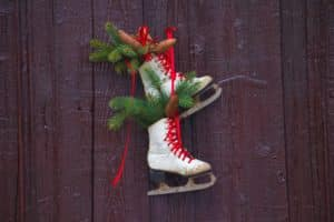 White ice skates with red laces handing on a wooden wall with greenery poking out of each skate.