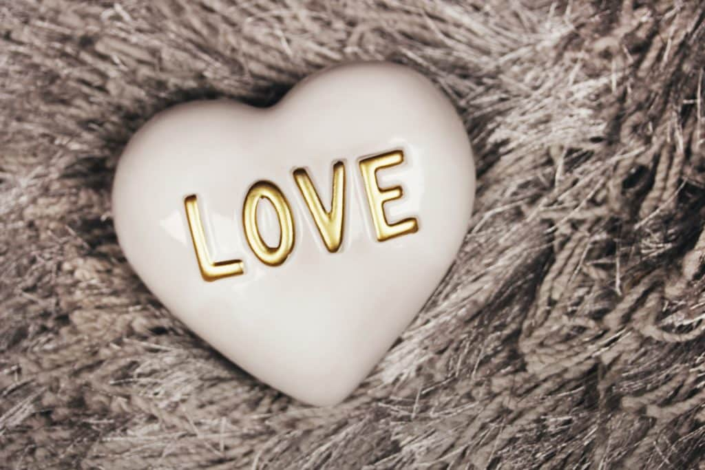 "A white ceramic heart with the word ""Love"" written in gold lettering atop a fuzzy surface."