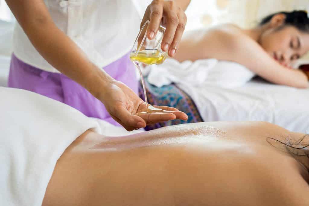 A massage therapist pours massage oil onto a woman's back.