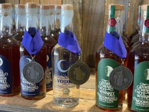 Whiskey and vodka bottles adorned with award medals hanging from blue ribbons.