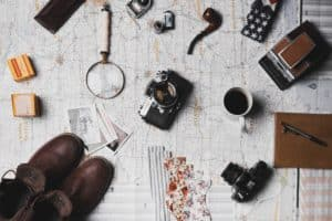 A scattering of items a detective might use, including a camera, magnifying glass, coffee mug, pen and paper.