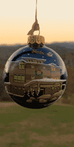A spherical ornament handpainted with an image of the front of Lucille's Mountain Top Inn & Spa.