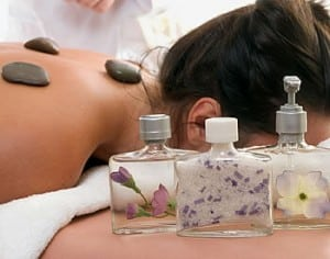 A woman receives a warm stone massage treatment alongside three bottles of massage oils.