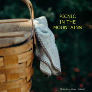 """Wicker picnic basket with title, """"Picnic in the mountains."""""""