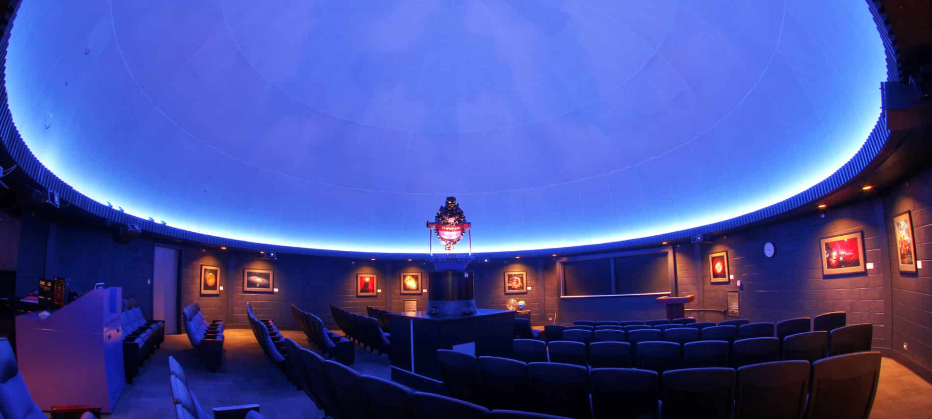 Empty theater planetarium seats and glowing, oblong sky/screen above.