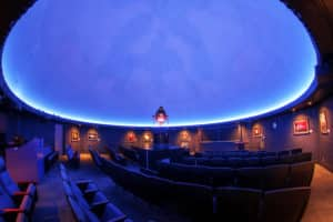 The empty seating theater in the planetarium with the glowing sky above.