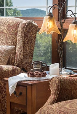 Wingback chairs flank a small table with antique lamp with scenic mountain view outside the windows in the background.
