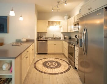 long view of kitchen with stanless steam appliances, counter with cream cabinets above and below, ceramic tiled floor with round rug by stove