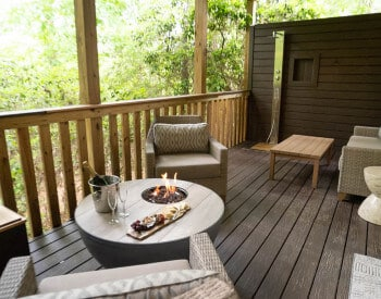 wooden deck with cream colored wicker chairs by round table with fire pit, wine in ice bucket, cheese tray, outside shower in background