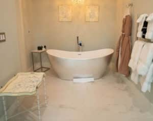 Bathroom with oval white tub with pictures above, hanging towels racks on wall , hanging brown robes on hooks, rectangular stand