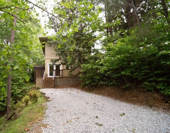 Gravel driveway in between trees on both sides leading to tan building with wodden deck with wide double doors