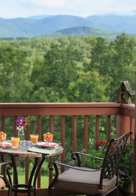 Table and two chairs on the deck over looking the mountains with orange juice and fruit on the table