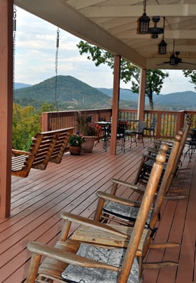 a line of rocking chairs and a porch swing. On the large deck overlooking the Mountains