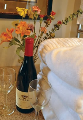 bottle of red wine, two glasses, 4 white fluffy towels and flowers in a vase