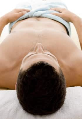 A gentleman laying on his back with a towel wrapped around his waist, dark brown hair