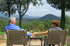 The two owners sitting in the chairs outside holding hands with a view of the mountains